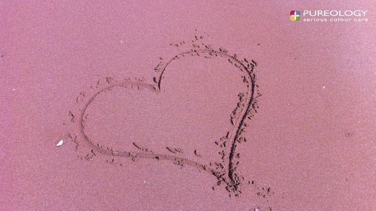 heart drawn in pink sand background